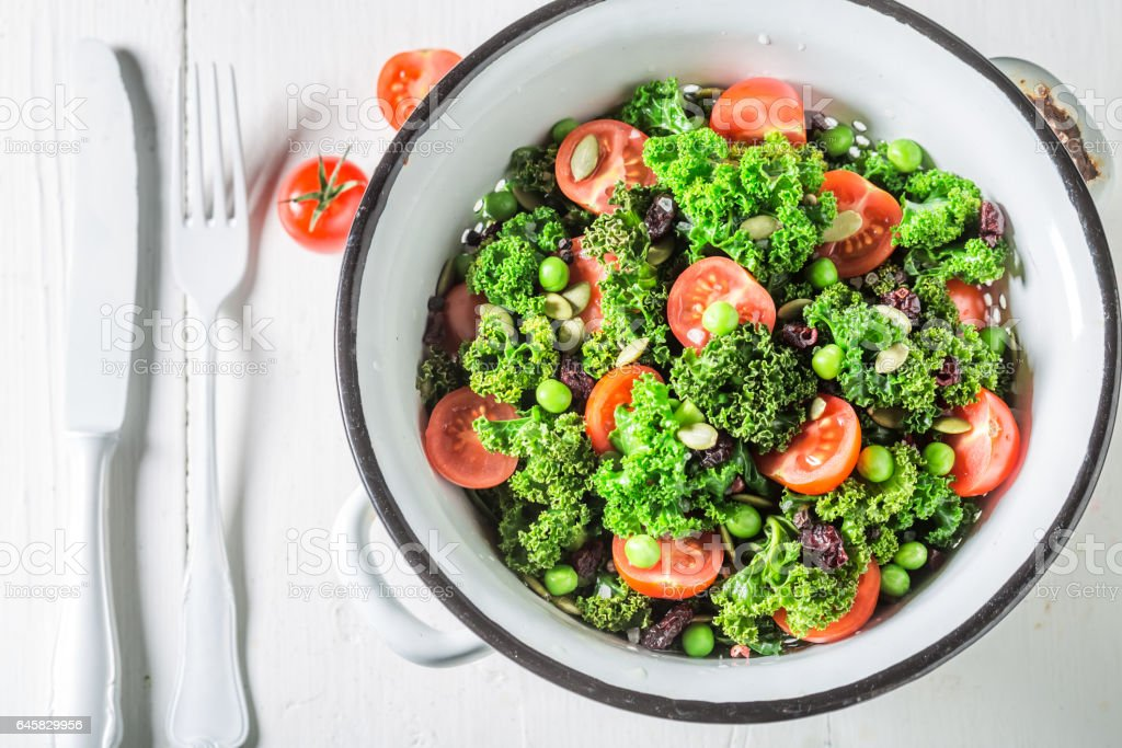 Fresh kale salad with tomatoes, peas and cranberry stock photo