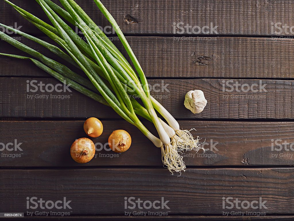Fresh leek, onion and garlic on a wooden background. stock photo