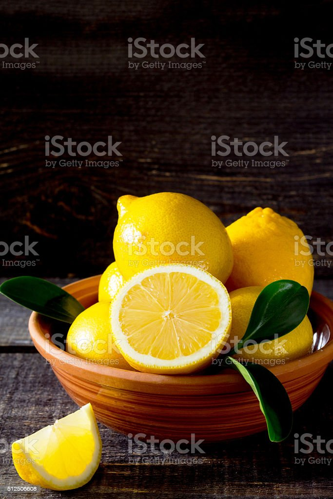 Fresh lemons in a bowl on a wooden table stock photo