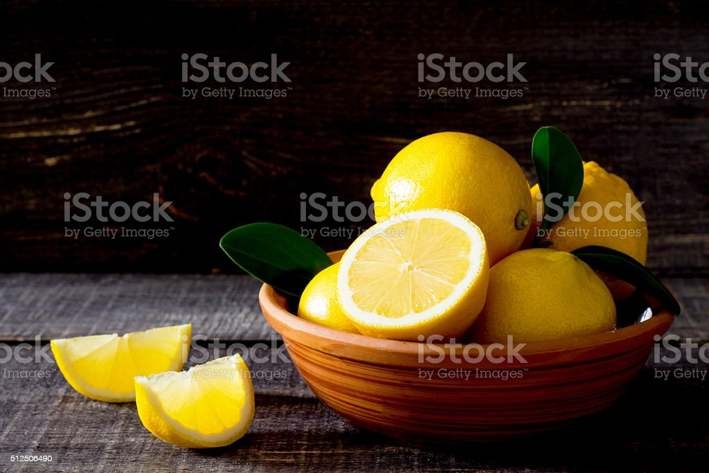 Fresh lemons in a bowl on the table stock photo