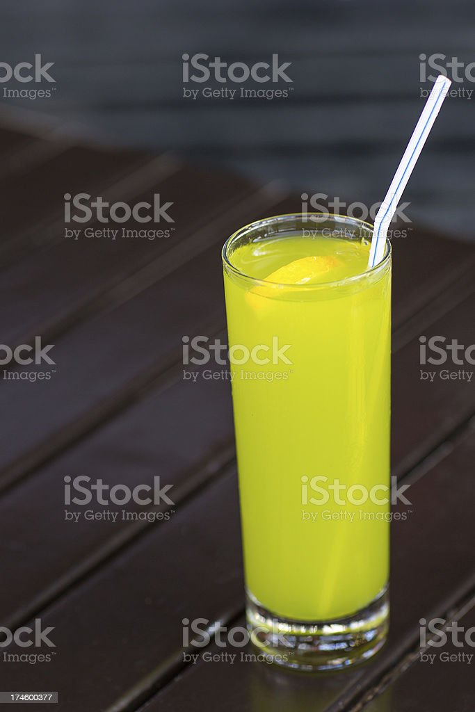 Fresh lime juice with straw on wood table royalty-free stock photo
