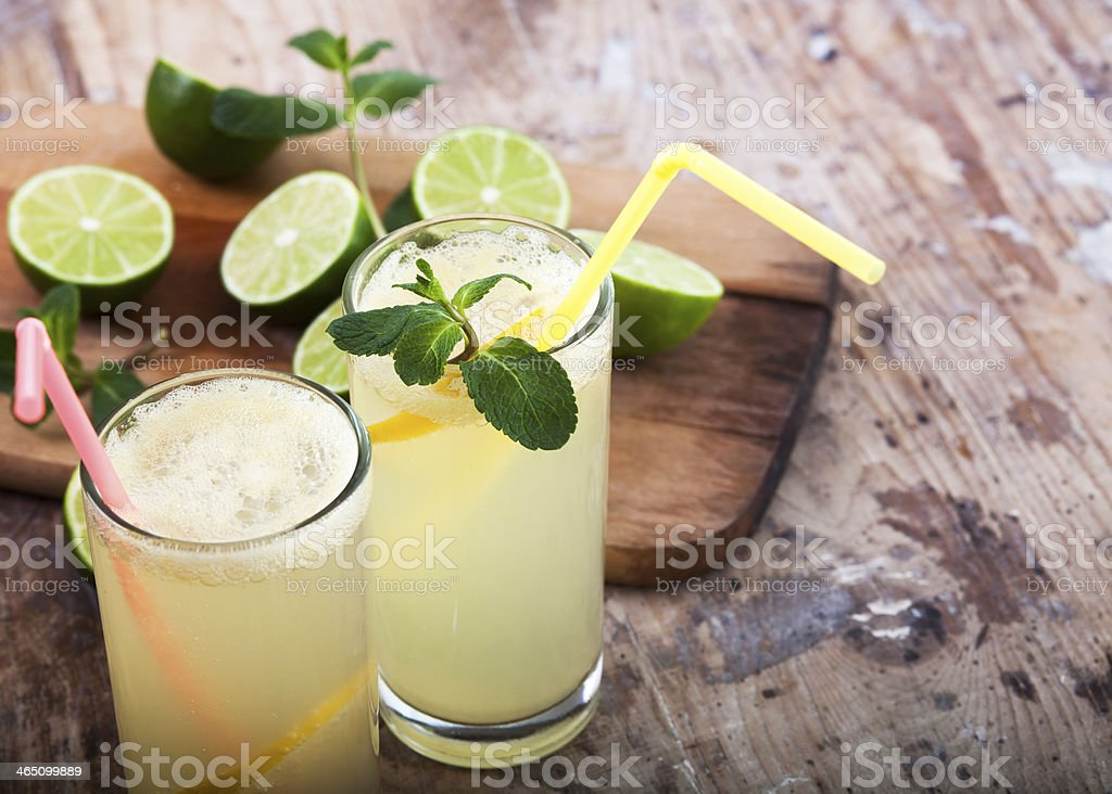 Fresh limes and lemonade on wooden background stock photo