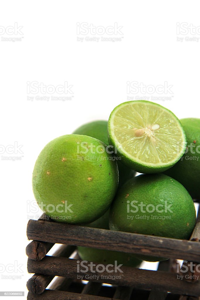fresh limes in Wooden basket stock photo