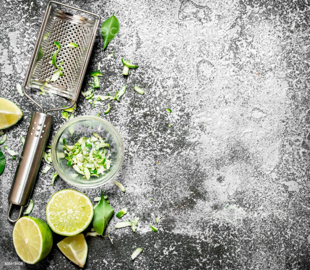 Fresh limes with grater and zest in a bowl. stock photo