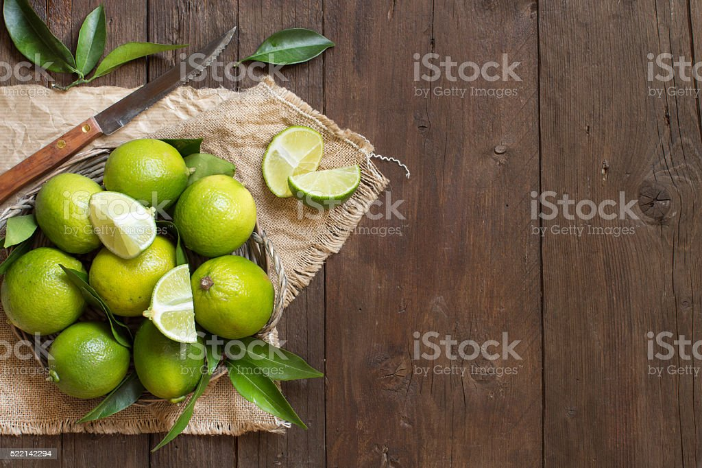 Fresh limes with knife and leaves stock photo