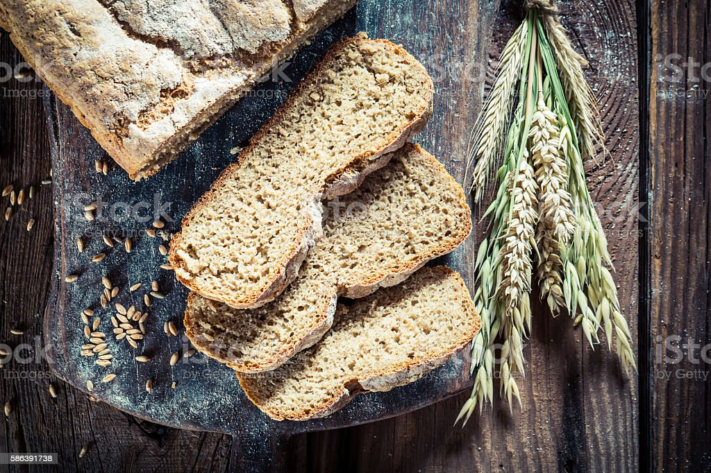 Fresh loaf of bread with ears of wheat stock photo