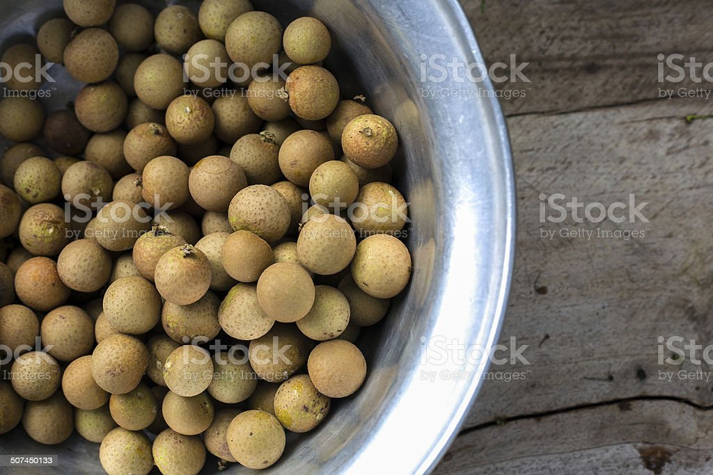Fresh Longans in a bowl on wood stock photo