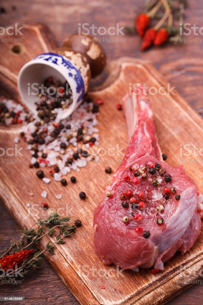 Fresh meat on the bone steak with spices stock photo