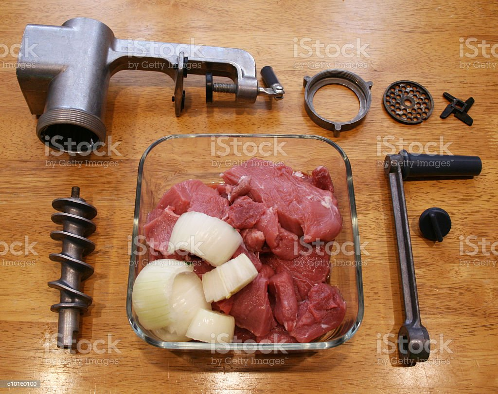 Fresh meat with onions become meat grinder. stock photo