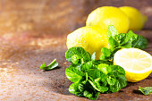 Fresh mint and lemon slices on rustic background