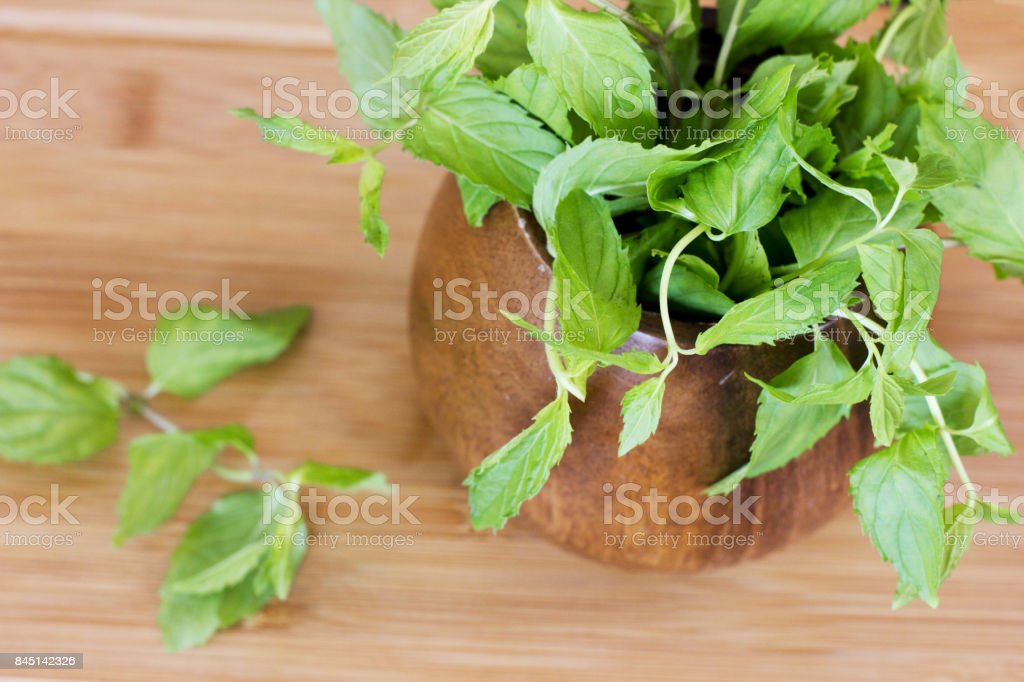 Fresh mint in the wooden brown bowl on a table stock photo