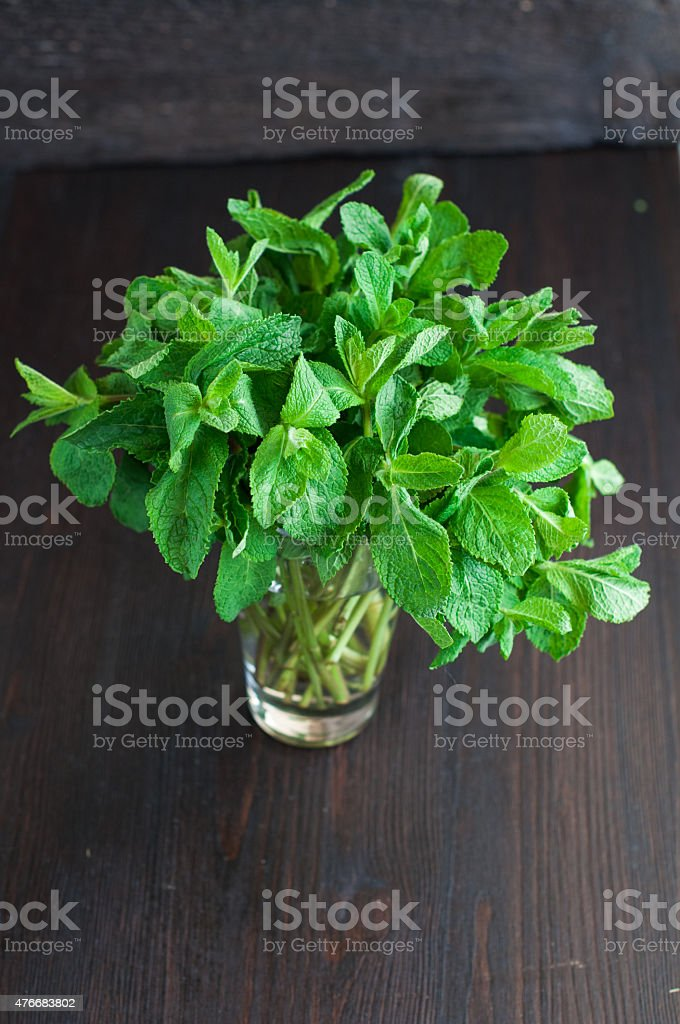 fresh mint leaves on a wooden background stock photo