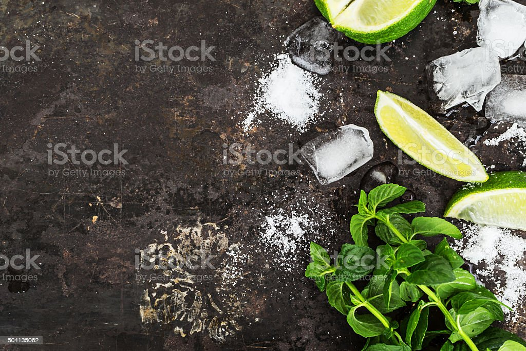 Fresh mint, slices of lime, ice,  over black  surface . stock photo