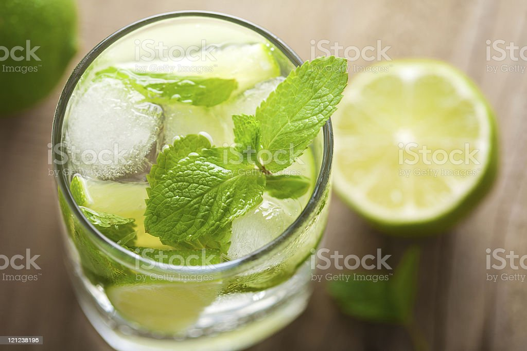 Fresh mojito cocktail in glass with lime on wooden table royalty-free stock photo