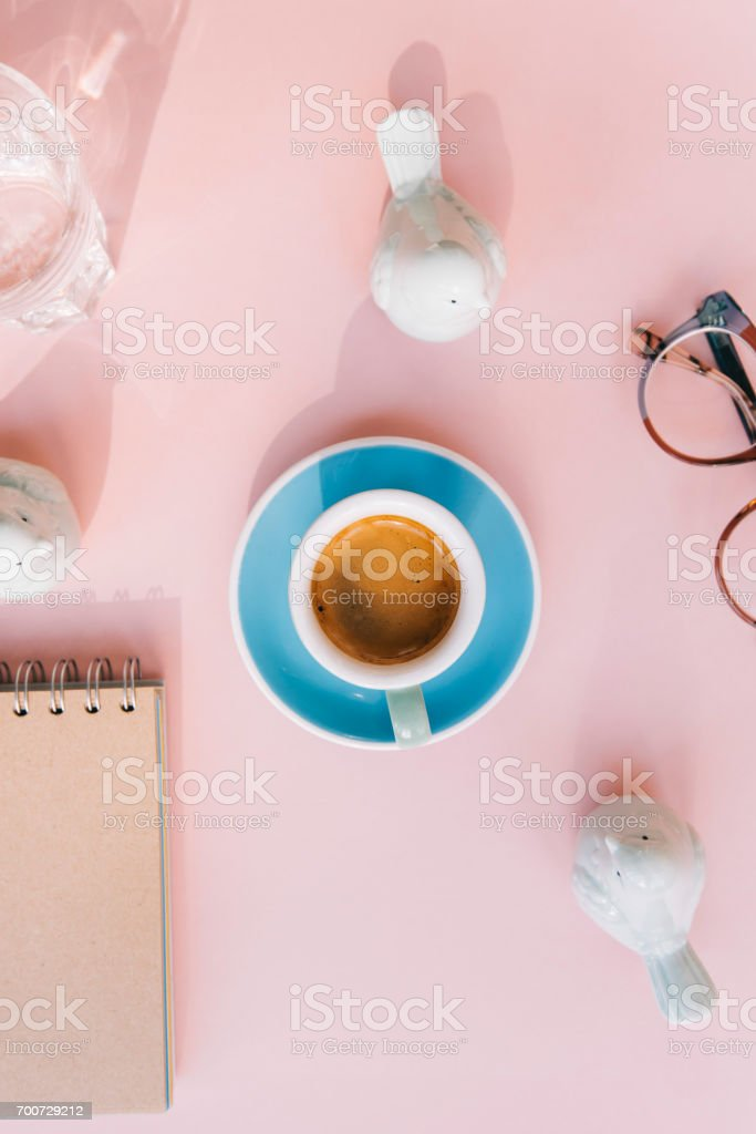 Fresh morning espresso coffee with a beautiful thick crema, glasses, paper notebook, laptop green ceramic decorative birds on the pink background. Flat lay stock photo