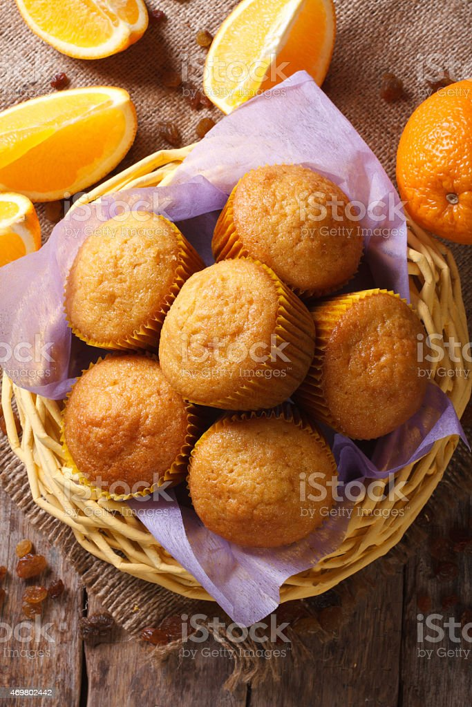 Fresh muffins in basket and oranges  Vertical view from above stock photo