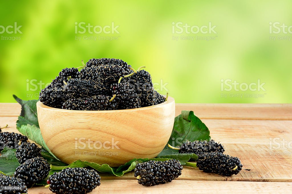 Fresh mulberries on wooden table. stock photo