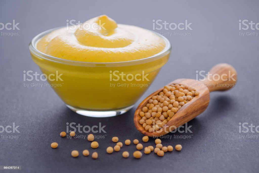 fresh mustard in glass bowl and wooden scoop with mustard seeds on dark background, horisontal stock photo