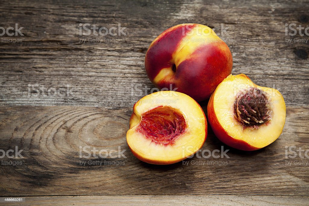 Fresh nectarines on wooden table stock photo