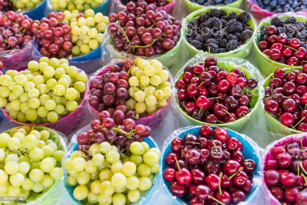 Fresh on the vine green and red seedless grapes, and cherries on display at farmers market stock photo