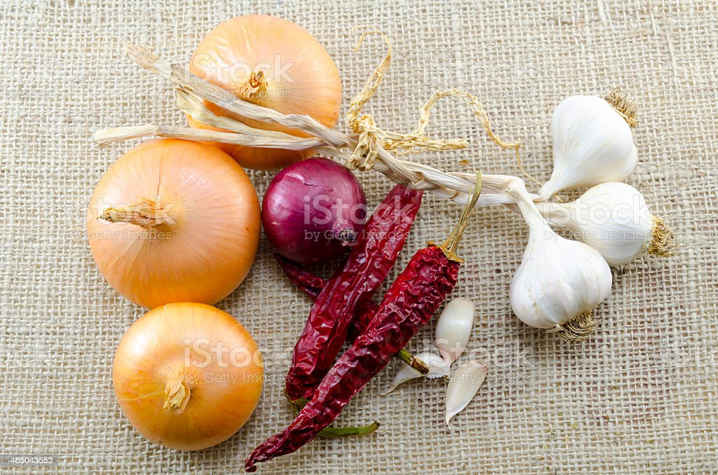 Fresh onions, garlic and dried peppers on a tablecloth royalty-free stock photo