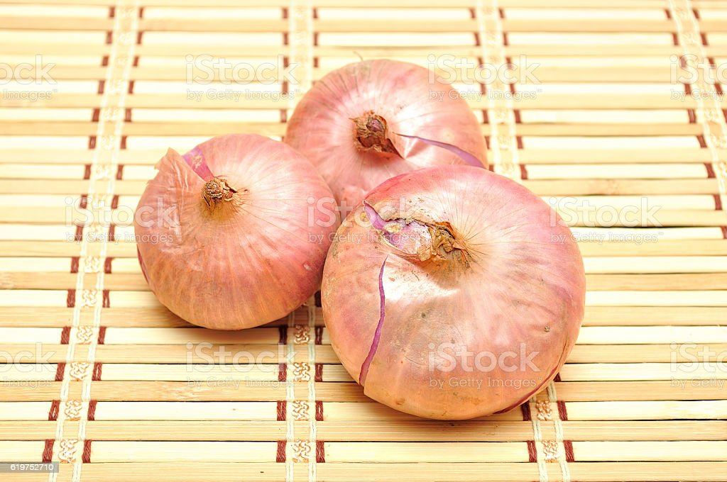 fresh onions vegetables on bamboo mat stock photo