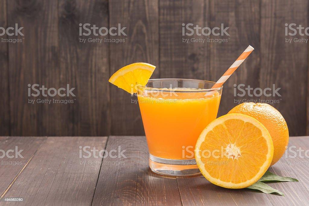 Fresh orange juice and oranges on wooden table stock photo