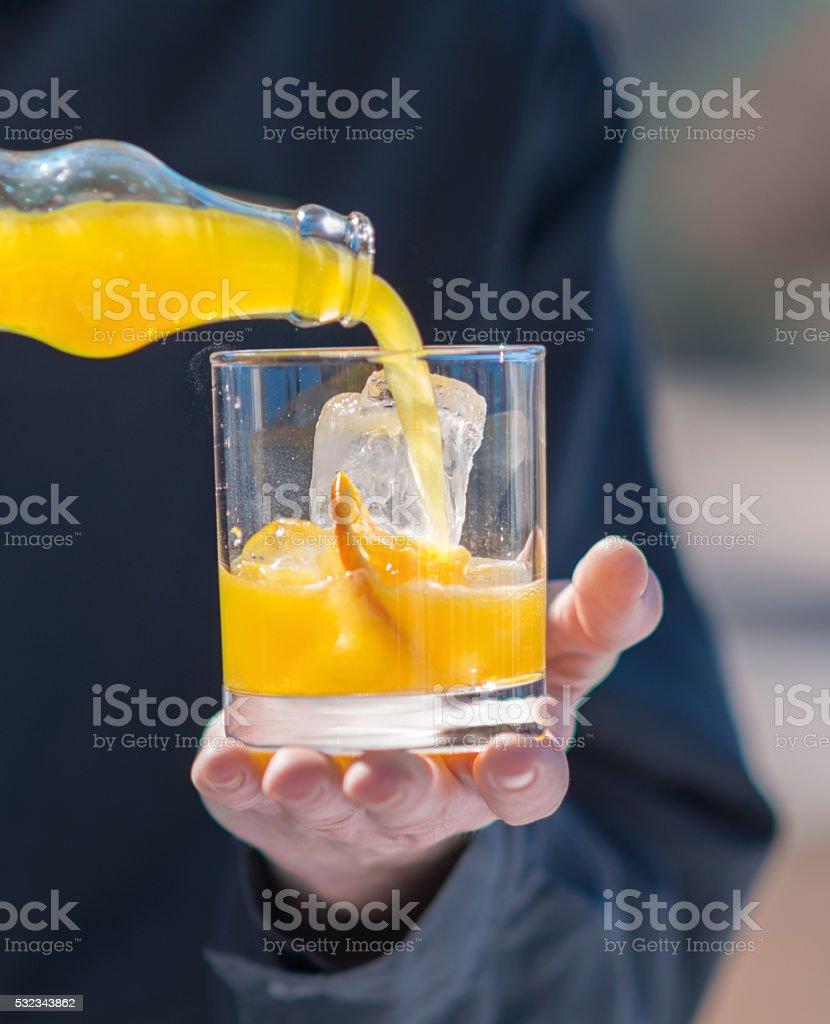 fresh orange juice on ice in a glass stock photo
