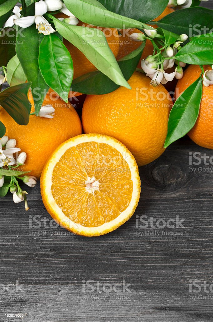 Fresh oranges and blossoms on a wooden surface stock photo