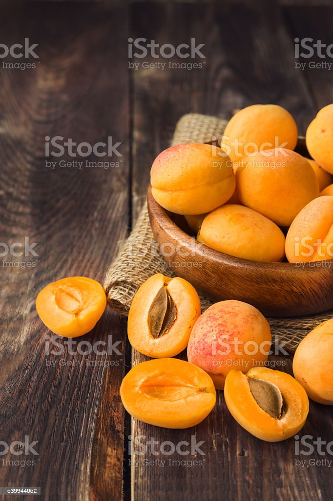 Fresh organic apricots in wooden bowl stock photo