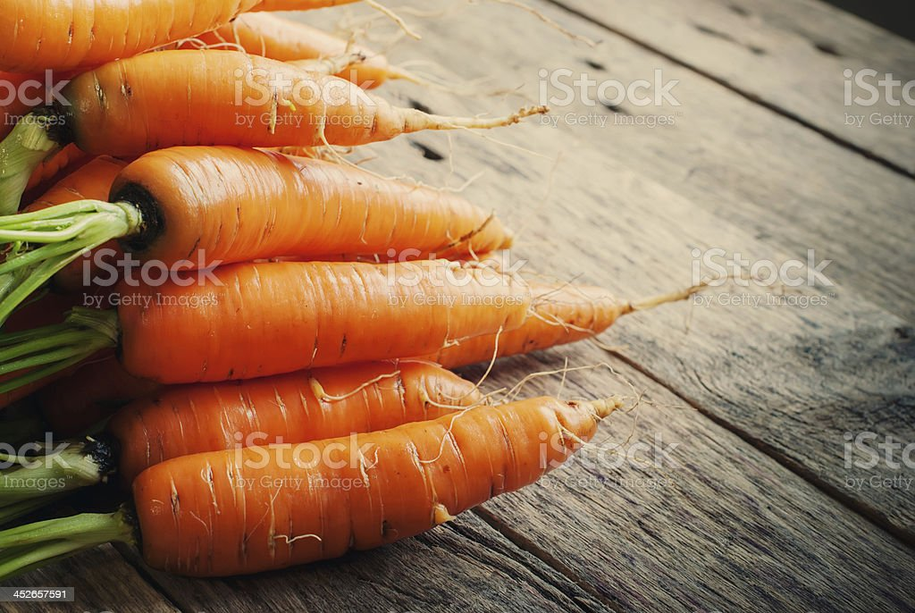 Fresh Organic Carrots in a basket on wooden background, rustical stock photo