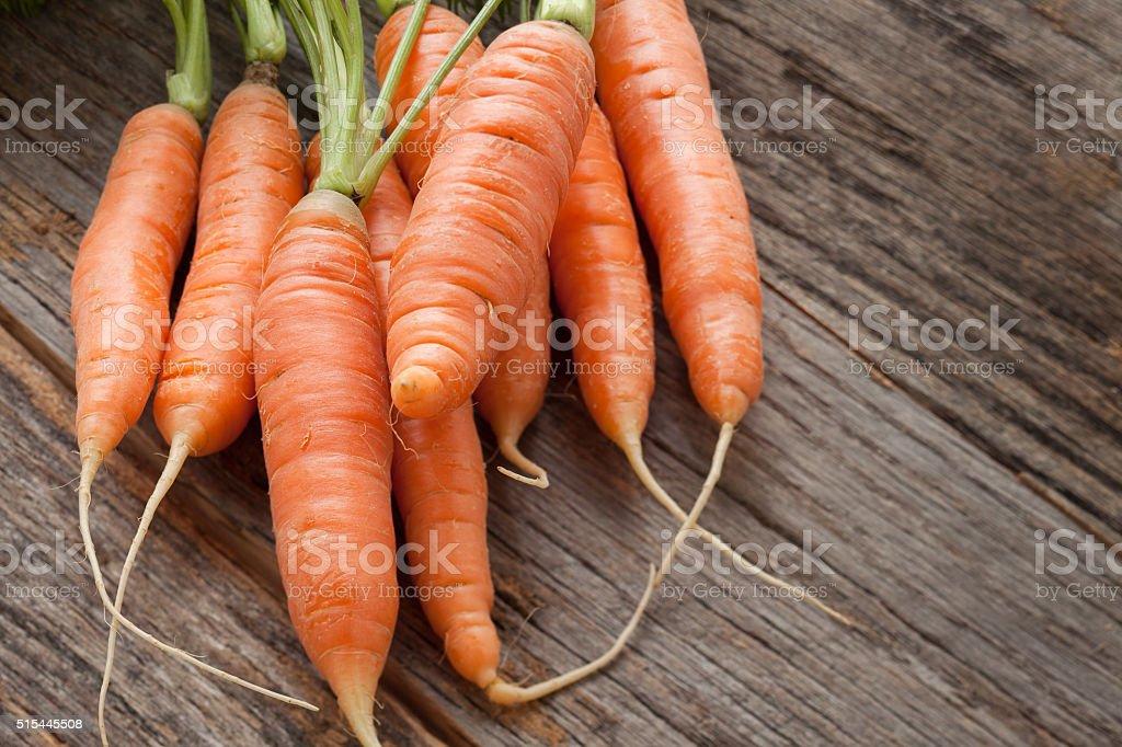 Fresh organic carrots on rustic wood table stock photo