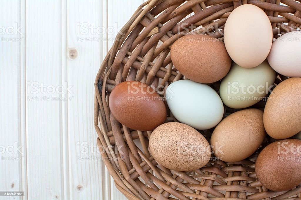 Fresh organic chickeneggs in old dusty basket on wooden backgrou stock photo
