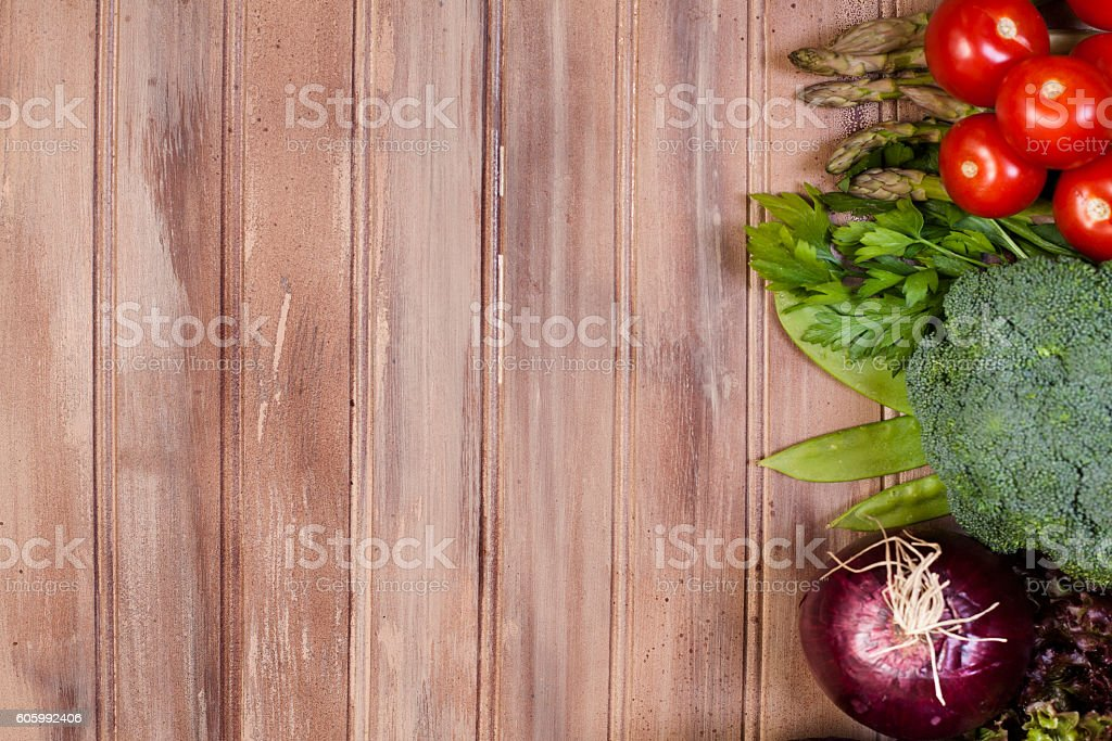 Fresh, organic colorful vegetables border rustic wooden table. stock photo