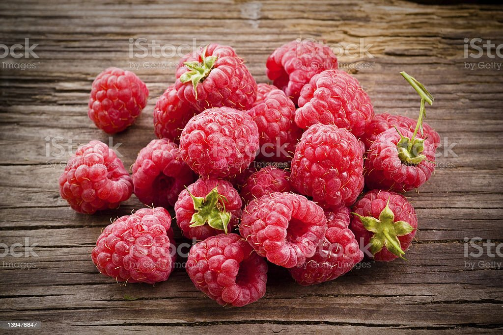 Fresh organic fruit - raspberry on wood background selective focus stock photo
