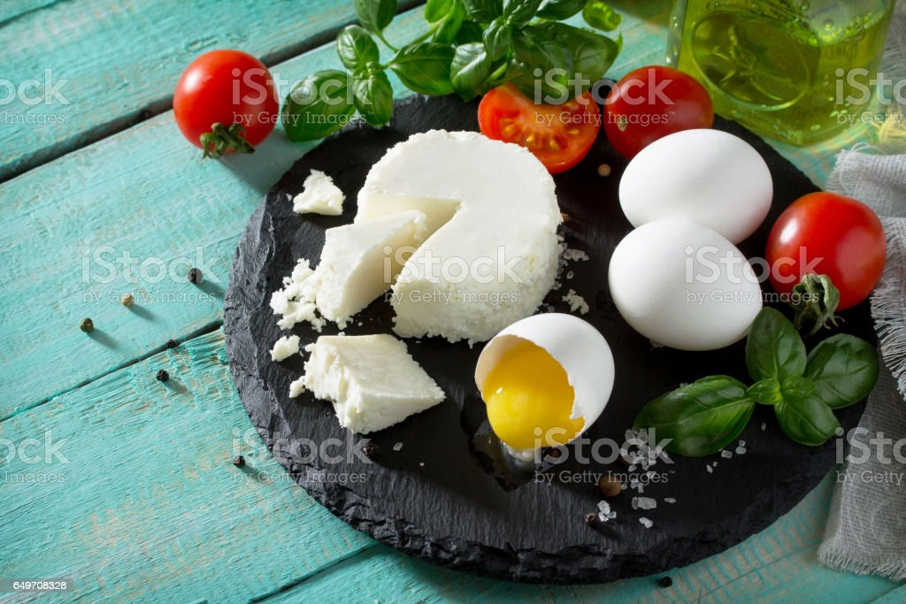 Fresh organic ingredients for the preparation of egg omelet stuffed with tomatoes and suluguni cheese. Concept of a healthy diet or detox diet, on a wooden background. Place for the text. stock photo