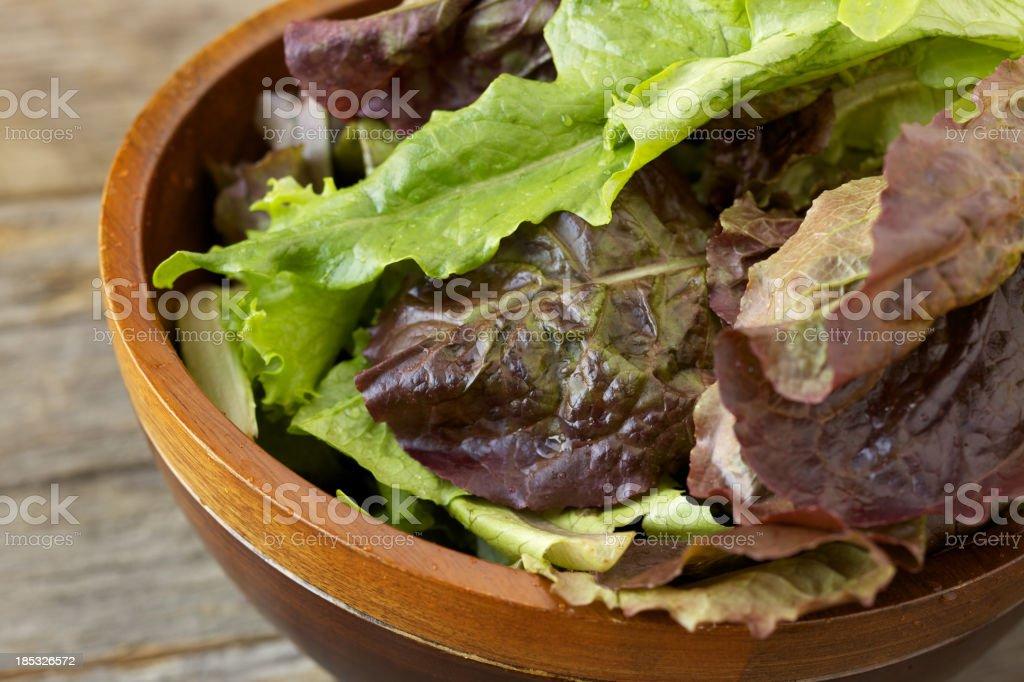 Fresh organic leafy greens in wood bowl royalty-free stock photo