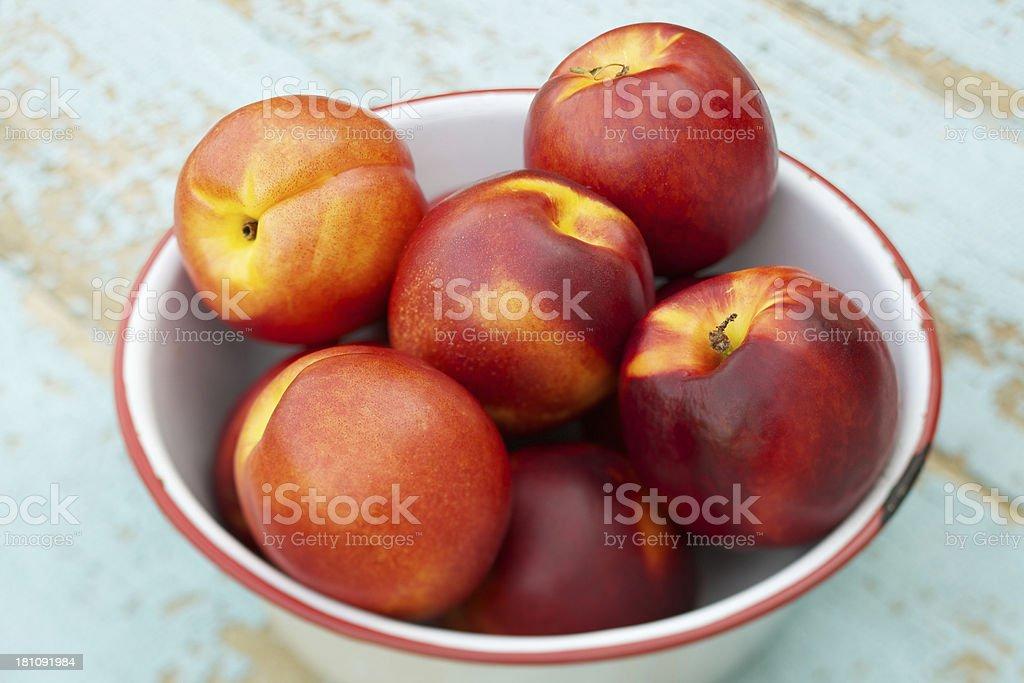 Fresh organic nectarines in a white metal bowl royalty-free stock photo