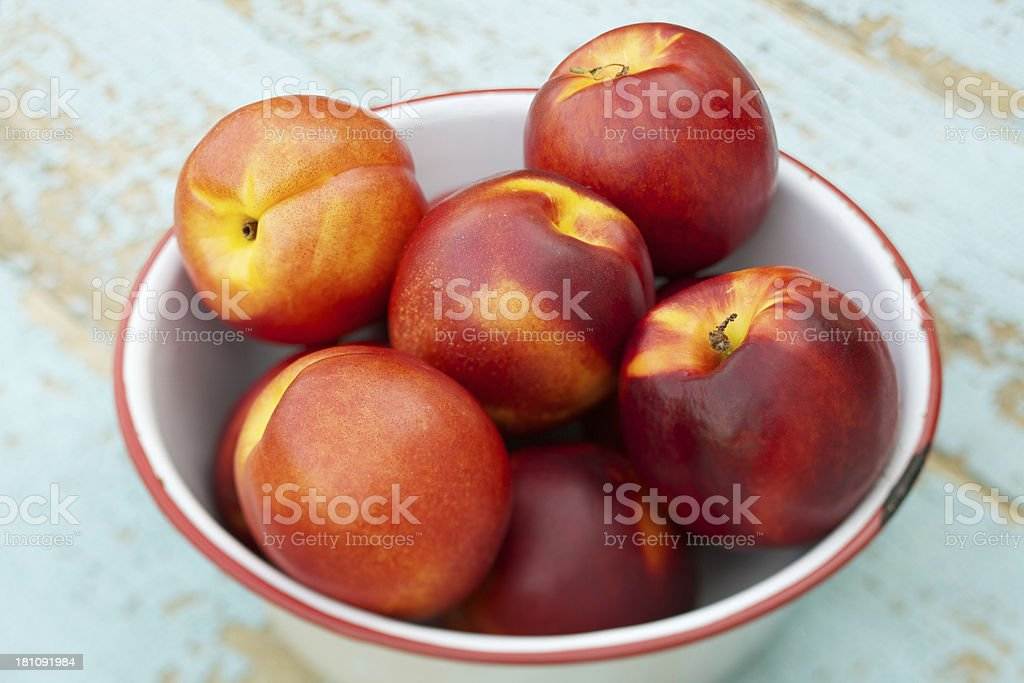 Fresh organic nectarines in a white metal bowl stock photo