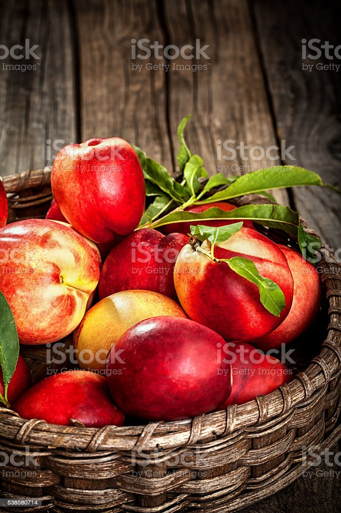 Fresh organic peaches in wooden basket with copy space stock photo