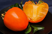 Fresh organic persimmon fruit cut in half on dark background
