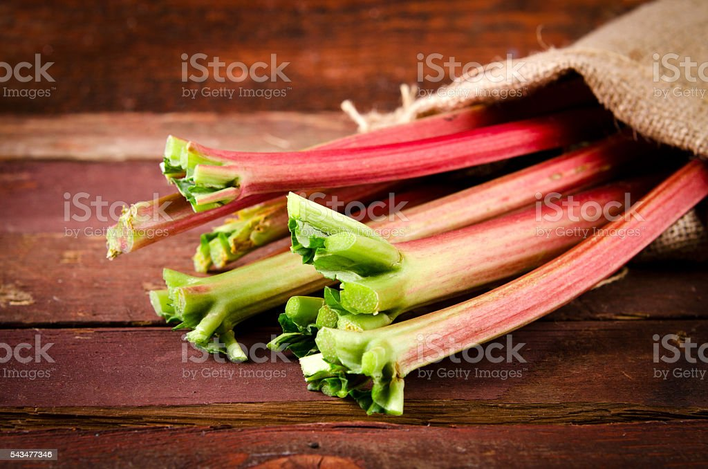 fresh organic red rhubarb on wooden table, Rustic style stock photo