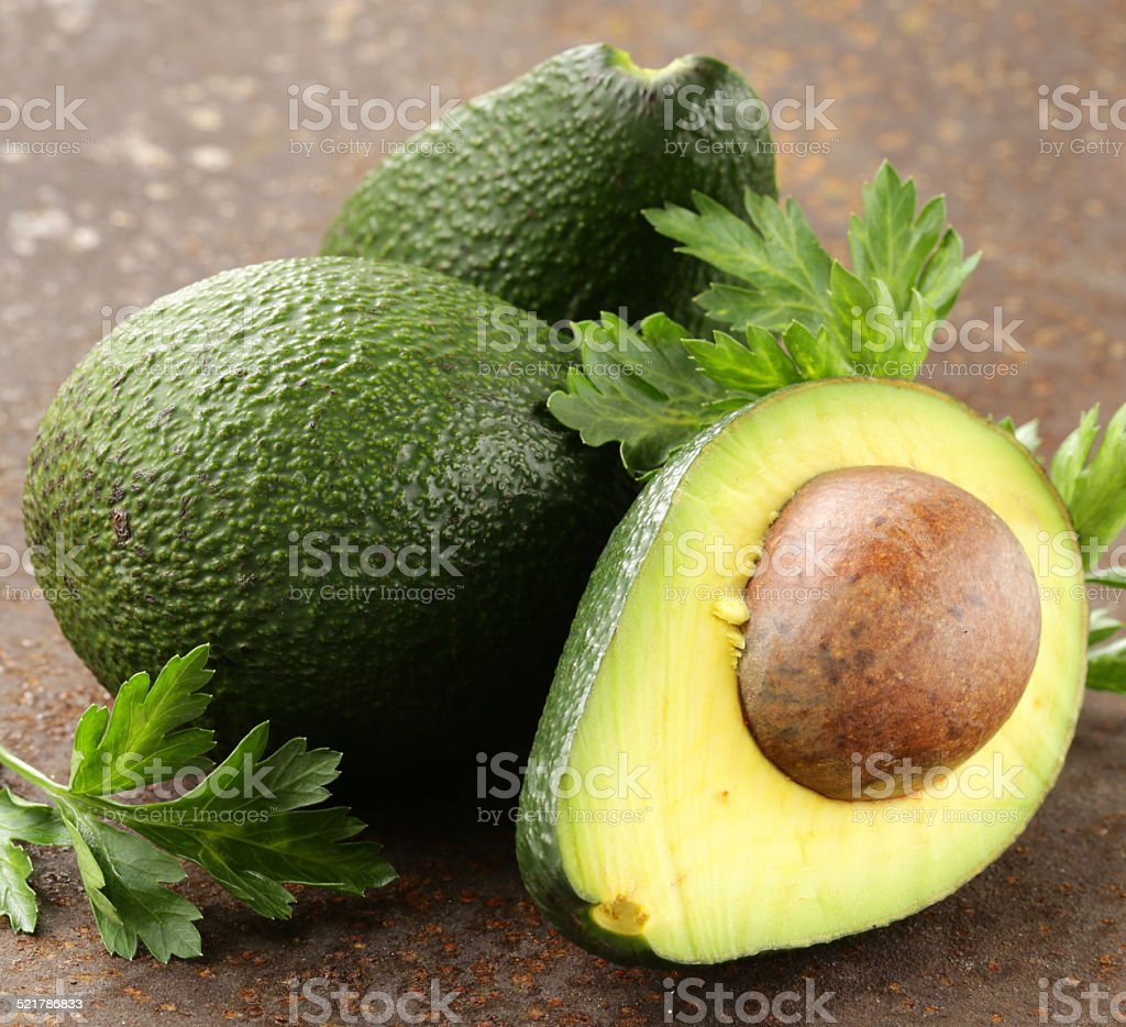 fresh organic ripe avocado with leaves of parsley stock photo