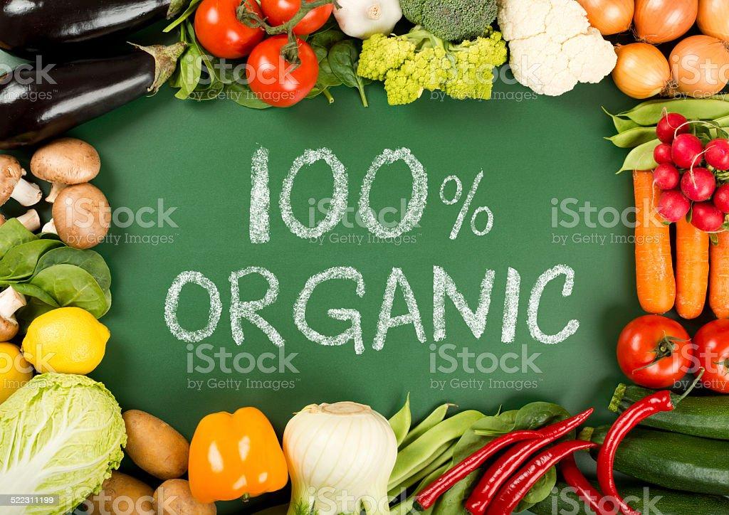 fresh organic vegetables on the 100% organic sign stock photo