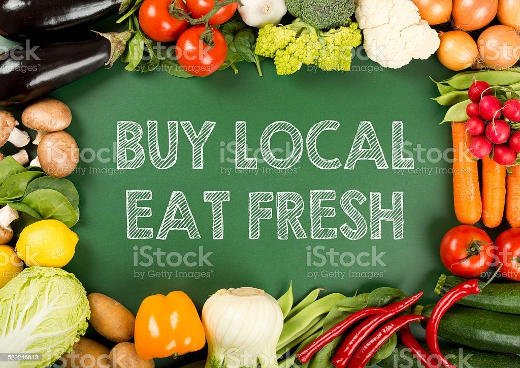 fresh organic vegetables on the 'buy local eat fresh' sign stock photo