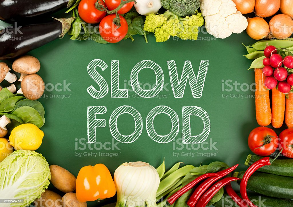 fresh organic vegetables on the 'slow food' sign stock photo