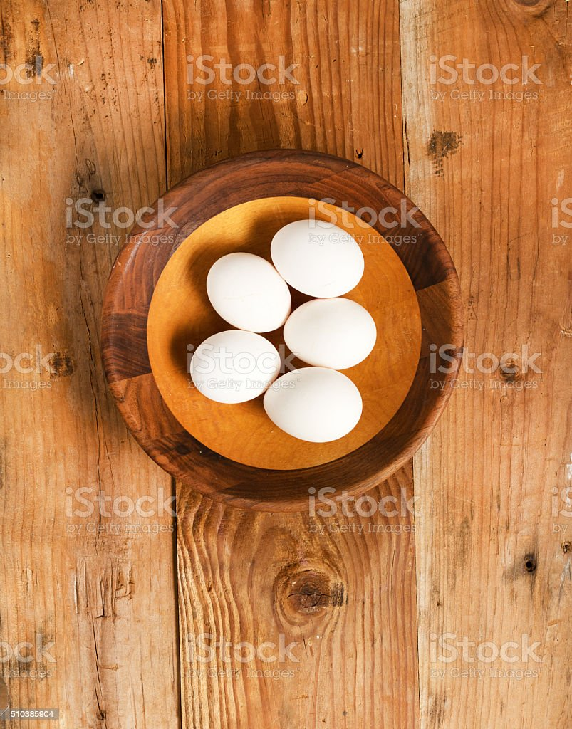 Fresh organic white eggs in rustic wooden bowl stock photo