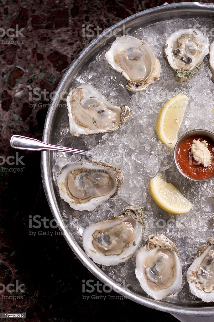 Fresh oysters and lime in a bucket of ice stock photo