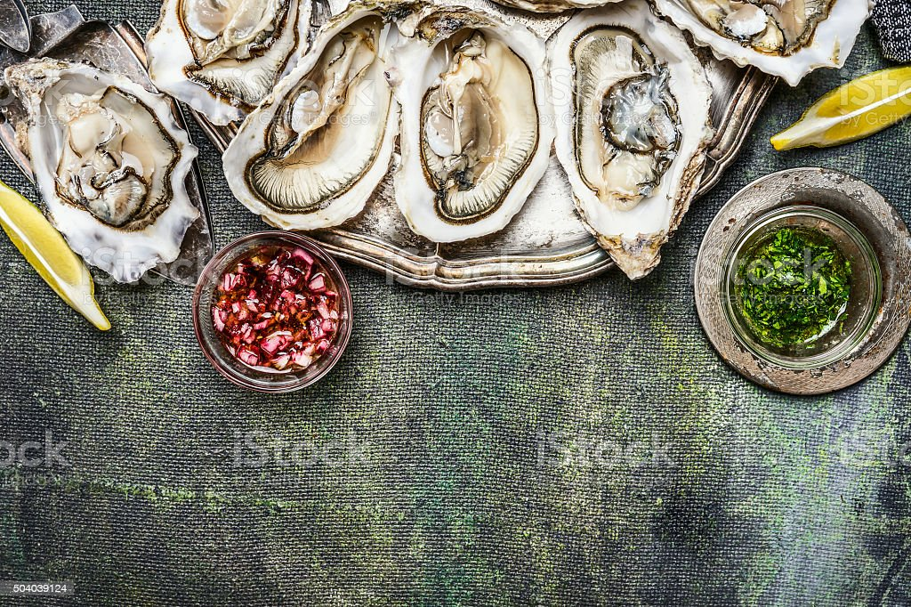 Fresh oysters with lemon and various sauces  , border stock photo