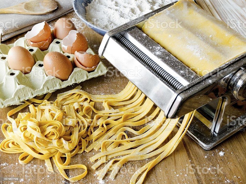 Fresh pasta cutting in machine. stock photo